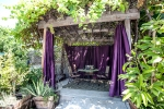 Gazebo with purple curtains, a table and chairs