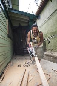 Carlos, with hand saw, cutting a 2x4