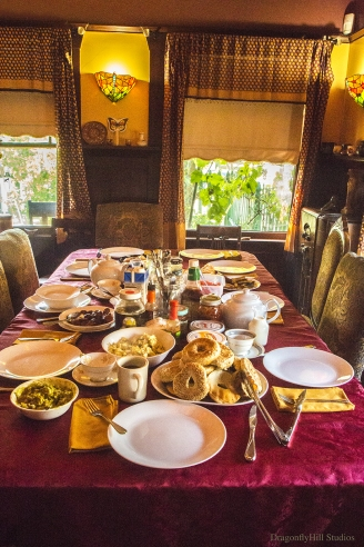 Breakfast table, set with plates, utensils and loaded with all kinds of yummy food!