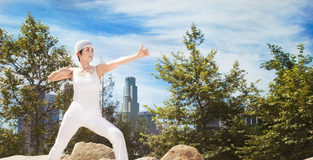 Yogi Tej Atma (Misako Lauritzen) at Vista Hermosa Park, in warrior position, with the L.A. skyline behind them.