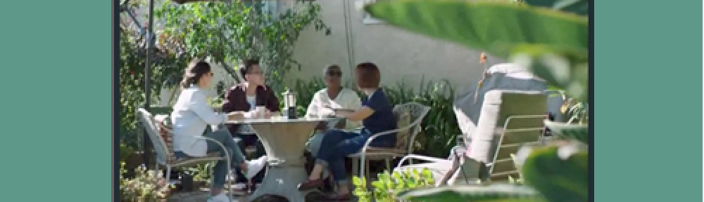Image of a group of people of different ages, ethnicities and genders, sitting around a table outside, talking. One of the women is Vanessa Johnson, Airbnb host.