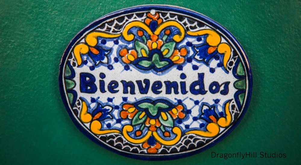 Talavera oval shaped tile, in blue, white, green, yellow and orange. Text: Binevenidos