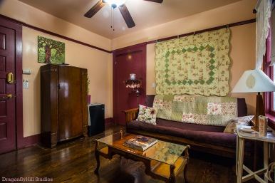 Image of the Rose Sage Room set up as a sitting room or Parlour: including an armoire, a woman/tree painting, a small refrigerator with a bamboo plant on top of it. The walls are peach and the trim is dark brown. There is a ceiling fan. The sofa is a mission style brown futon with a quilt throw, 2 floral throw pillows and a quilt mounted on the wall. There is a tall white table with a vase, a scalloped plate and a lamp. There is also a floor lamp with a feather trimmed lamp shade. The coffee table is made of wood and has a glass top and there's a book on the table. The windows have a lace window treatment with a pull down scalloped shade.