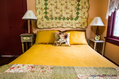 Image of the Rose Sage Room: including an armoire, a woman/tree painting, a small refrigerator with a bamboo plant on top of it. The walls are peach and the trim is dark brown. There is a ceiling fan. The bed has gold pillows, a gold duvet cover, with a floral throw pillow and a quilt mounted on the wall. There are two bedside tables, with lamps and an alarm clock. The windows have a lace window treatment with a pull down scalloped shade.