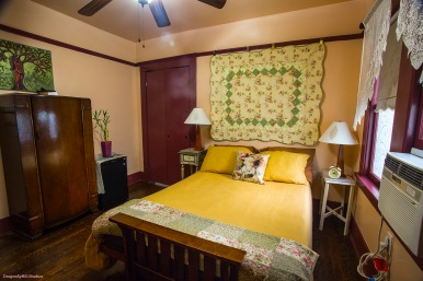 Image of the Rose Sage Room: including an armoire, a woman/tree painting, a small refrigerator with a bamboo plant on top of it. The walls are peach and the trim is dark brown. There is a ceiling fan. The bed has gold pillows, a gold duvet cover, with a floral throw pillow and a quilt mounted on the wall. There are two bedside tables, with lamps and an alarm clock. The windows have a lace window treatment with a pull down scalloped shade. There is a window air conditioner unit.
