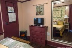 Image of the Rose Sage Room: through the mirror on the wall that also has a T.V. a wall hanging of a rabbit, a built in dresser, a closet door, an electric fire place. The walls are peach and the trim is dark brown. The reflection in the mirror shows The bed with gold pillows, a gold duvet cover, with a floral throw pillow and a quilt mounted on the wall. There are two bedside tables, with lamps and an alarm clock.
