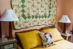 Image of the bed in the Rose Sage Room: gold pillows, duvet cover, with a floral throw pillow and a quilt mounted on the wall. There are two bedside tables, with lamps and an alarm clock.