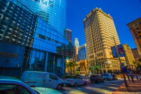 Intercontinental Hotel and other older buildings in Downtown Los Angeles. Intercontinental is a new hotel with glass and mirrored panels. cars, traffic, people