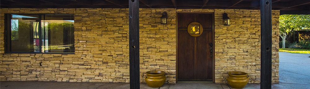 Front door to a southwest style home. House has a stone veneer, a wood door with a window, and two lamps on either side of the door. There is a window to the left of the door. The house has a cement sidewalk entryway covered by a wood arbor. Photo by Emma Rosenthal